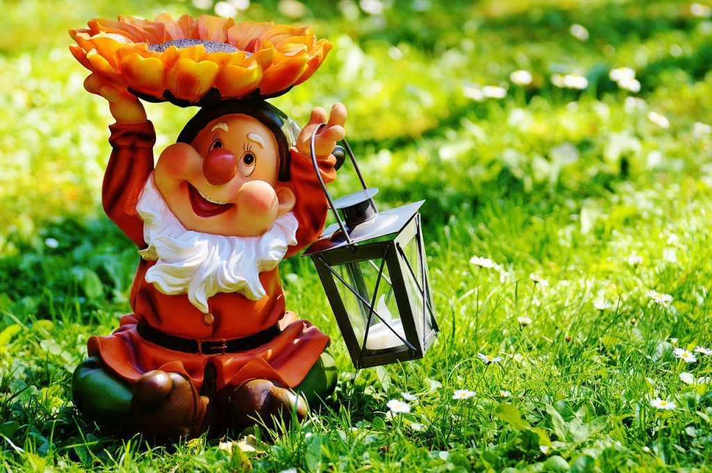 Un gnomo de jardín con barba blanca, ropajes rojos, un candil en la mano izquierda y una flor sobre la derecha.