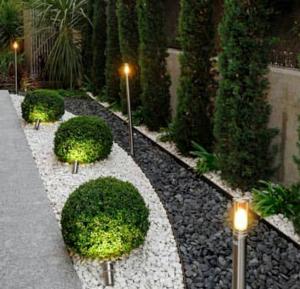 Jardín iluminado con piedras blancas y negras y sin hierba, solo árboles y arbustos pequeños
