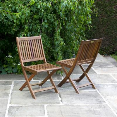 Dos sillas de madera plegables para jardín sobre suelo de piedra y arbustos al fondo