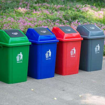 Cuatro cubos de basura de distintos colores para reciclar en el jardín