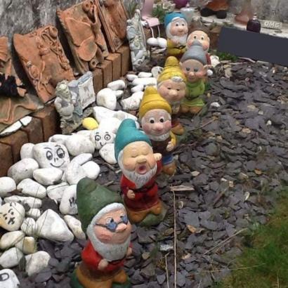 Caminito de piedras y paredes de corteza en un jardín con enanitos