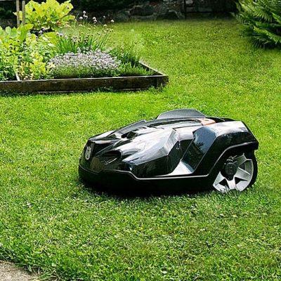 Un robot cortacésped sobre la hierba de un jardín